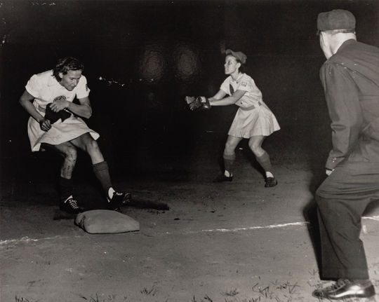 Connie Wisniewski (left) running to a base as another player prepares to catch the ball and an umpire watches. Photo taken during a night game. (National Baseball Hall of Fame and Museum)