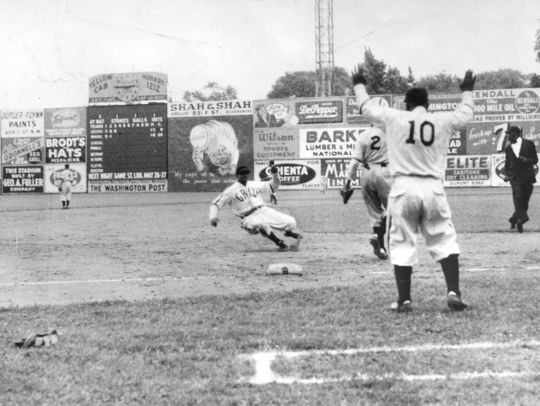 Cool Papa Bell slides into third base, while playing for the Homestead Grays, on an Opening Day doubleheader against the Baltimore Elite Giants. (National Baseball Hall of Fame)