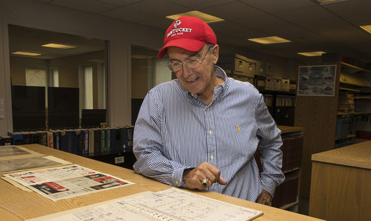 Bill George, the official scorer for the longest game in professional baseball history, examines his score book during a visit to the Hall of Fame on Oct. 29. (Milo Stewart Jr./National Baseball Hall of Fame and Museum)