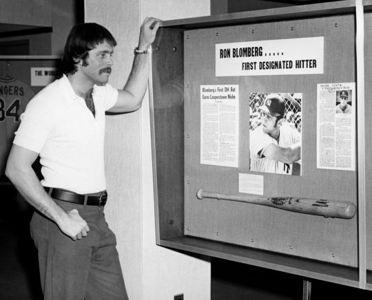 Ron Blomberg examines the bat he used as the American League's first-ever designated hitter an an exhibit at the Hall of Fame in the mid-1970s. (National Baseball Hall of Fame and Museum)