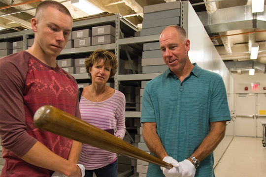 Former Oakland A's and New York Yankees third baseman Scott Brosius holds a bat used by Hall of Famer Ted Williams in the Hall of Fame collection. Brosius visited Cooperstown on Thursday with his wife Jennifer and son David. (Parker Fish / National Baseball Hall of Fame)