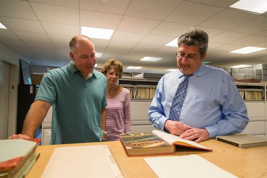 Erik Strohl, vice president of exhibits and collections at the Hall, shows Scott and Jennifer Brosius an original copy of the first issue of Sports Illustrated magazine from August 16, 1954, featuring Hall of Famer Eddie Mathews on the cover. (Parker Fish / National Baseball Hall of Fame)