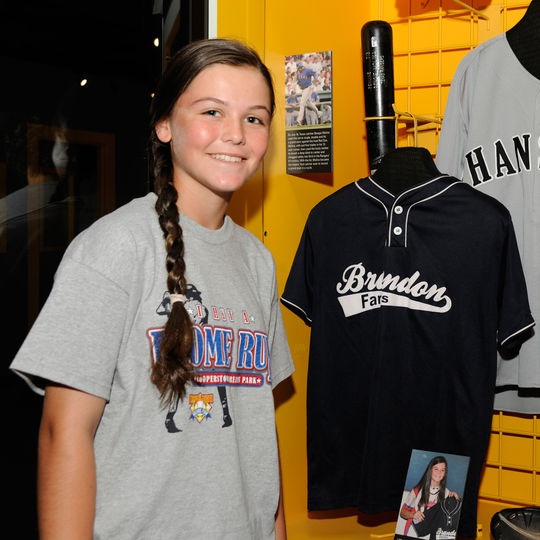 Chelsea Baker stands next to the jersey she donated to the Hall of Fame after pitching perfect game for her youth baseball team on April 9, 2010. (Milo Stewart, Jr. / National Baseball Hall of Fame)