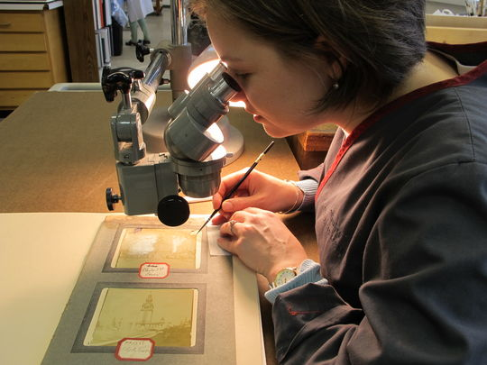 Maggie Wessling, a former Assistant Photograph and Paper Conservator at Northeast Document Conservation Center, stabilizes a photo in the NEDCC lab in Andover, Mass. (Photo courtesy of Northeast Document Conservation Center)