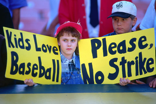 """Baseball fan Erin States holds up signs that read """"Kids love baseball"""" and """"Please, no strike"""" before a game between the Seattle Mariners and Oakland Athletics at the Oakland Coliseum in Oakland, California on August 12, 1994. This was the last game played before the strike was called. (Brad Mangin / National Baseball Hall of Fame Library)"""