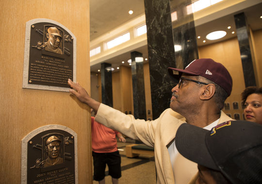 Gilberto Dihigo touches his father's Hall of Fame plaque during a visit to Cooperstown on June 29. (Milo Stewart Jr./National Baseball Hall of Fame and Museum)