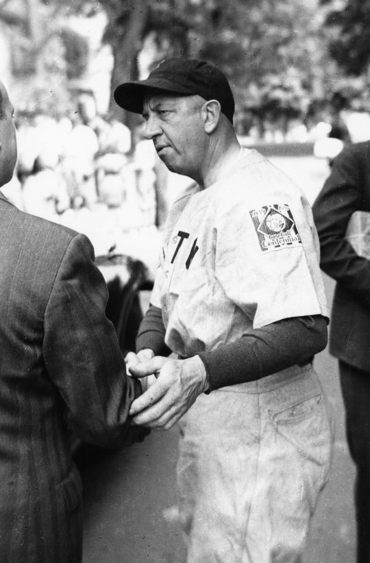 Hall of Famer Eddie Collins greets fans on June 12, 1939, in Cooperstown. Collins managed a team in the game at Doubleday Field that day. The patch on his left shoulder, celebrating baseball's centennial, was worn throughout the major leagues that year. (Homer Osterhoudt/National Baseball Hall of Fame and Museum)