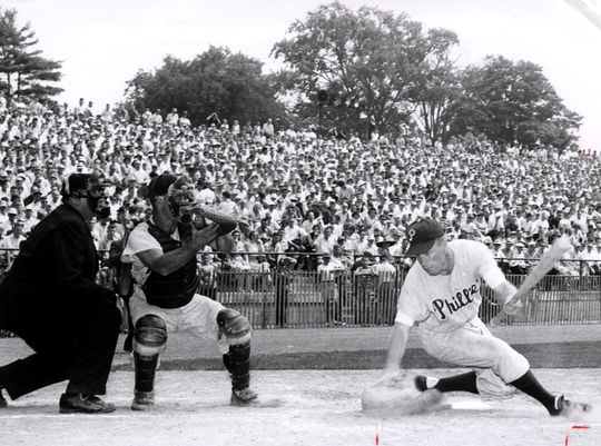 Future Hall of Famer Richie Ashburn takes a hard swing at Jim Constable's pitch. The catcher is Clint Courtney and  the umpire is Stan Landes. (National Baseball Hall of Fame Library)