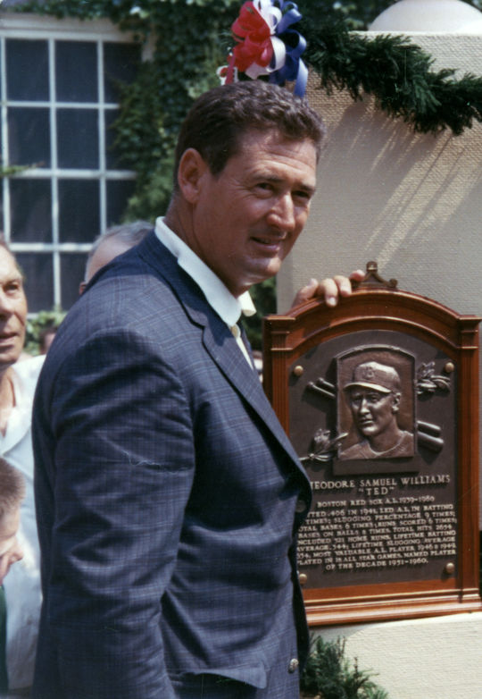 Ted Williams posing with his plaque during Induction Weekend. B-3682.83 (National Baseball Hall of Fame Library)