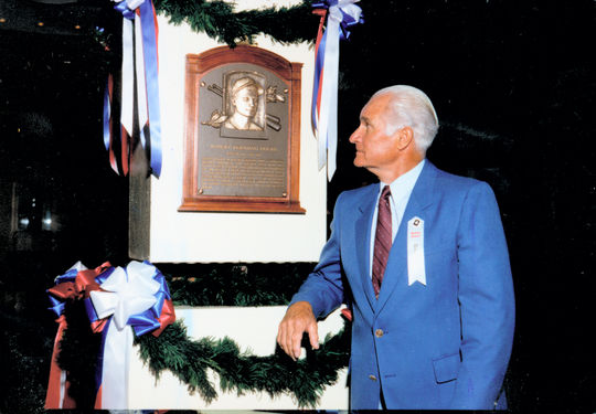 Bobby Doerr reads his Hall of Fame plaque following the 1986 Induction Ceremony in Cooperstown. (National Baseball Hall of Fame Library)