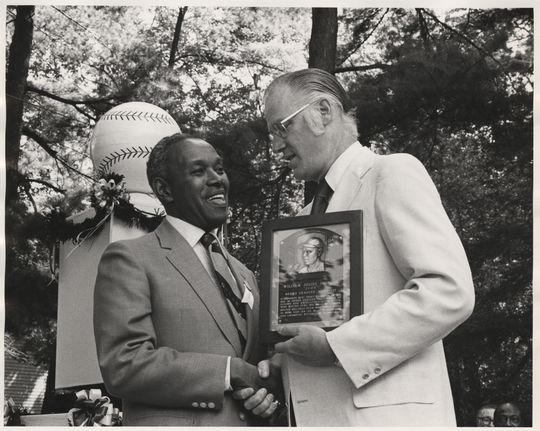 Judy Johnson accepting his plaque from Commissioner Bowie Kuhn during the 1975 Hall of Fame Induction Ceremony. BL-357.88 (National Baseball Hall of Fame Library)
