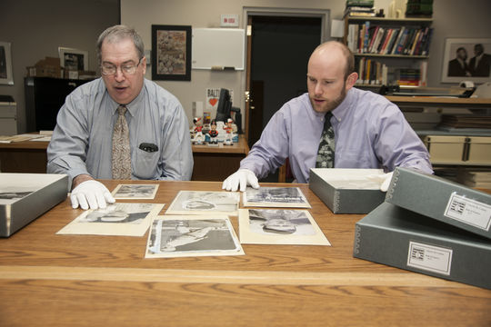 John Horne, the Museum's coordinator of rights and reproductions (left), and former photo archives assistant Ken Roussey examine images from the Charles Conlon photograph collection. (Milo Stewart, Jr. / National Baseball Hall of Fame)