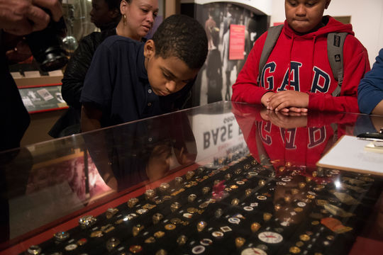"""Students from Creston Academy in The Bronx, N.Y., examine the Museum's World Series rings display in the Autumn Glory exhibit. Creston Academy students visited the Museum on June 2 after participating the Museum's """"Sandlot School of After School All-Stars"""" program this spring via videoconference technology. (Parker Fish / National Baseball Hall of Fame)"""