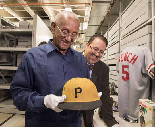 Justino Clemente, brother of Hall of Famer Roberto Clemente, holds the cap worn by Roberto when he recorded his 3,000th career hit on Sept. 30, 1972. Looking on is Adrian Burgos of La Vida Baseball, who served as Justino Clemente's interpreter during his visit to the Hall of Fame. (Milo Stewart Jr./National Baseball Hall of Fame and Museum)