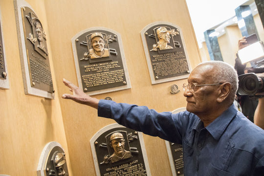 Justino Clemente touches the Hall of Fame plaque of his brother, Roberto Clemente, during a visit to Cooperstown on Sept. 29, 2018. (Milo Stewart Jr./National Baseball Hall of Fame and Museum)