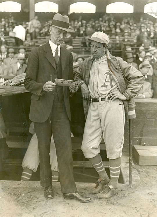 Philadelphia Athletics' manager Connie Mack (left) converses with fellow Hall of Famer Eddie Collins outside the team's dugout. (National Baseball Hall of Fame and Museum)