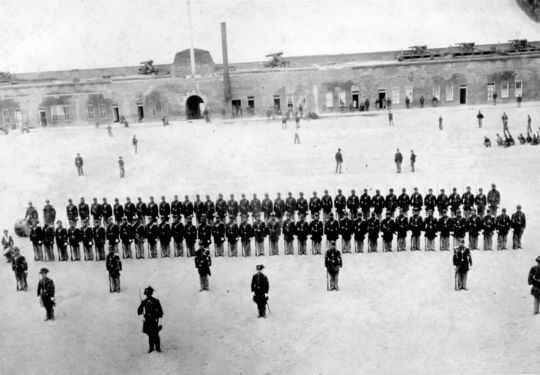 Company H of the 48th New York Regiment, stiffly posed for this 1863 formal portrait at Fort Pulaski, in Savannah, Ga., seems oblivious to the more informal baseball game in progress behind them.  The photo is one of the earliest known photographs of a baseball game. BL-125-84 (National Baseball Hall of Fame Library)