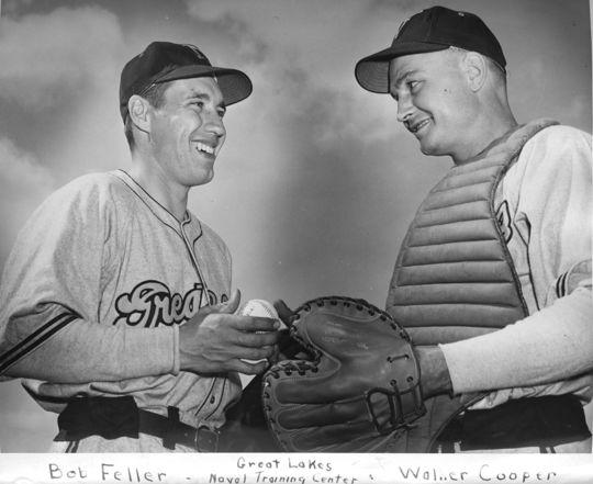 Bob Feller speaks to major league catcher Walker Cooper during a baseball game held at the Great Lakes Naval Training Center. (National Baseball Hall of Fame)