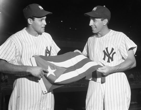Cuban shortstop Willy Miranda (left) showing his national flag to his New York Yankees teammate Phil Rizzuto in 1953 (Osvaldo Salas/National Baseball Hall of Fame Library)