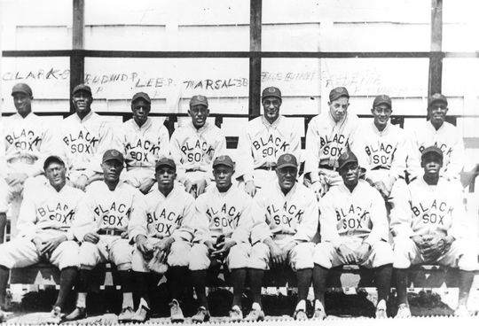"""The 1929 American Negro League champion Baltimore Black Sox, featuring the """"Million Dollar Infield,"""" so named for the prospective worth of the players had they been white. Marcelle is in the back row, fourth from the left.  Frank Warfield, who bit off part of Marcelle's nose in a bloody fight, is in the front row, middle. Baltimore_Black_Sox_1929.2226.73_PD  (National Baseball Hall of Fame and Museum)"""