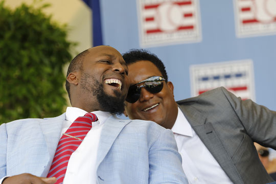 Vladimir Guerrero and Pedro Martinez share a laugh during the 2018 Hall of Fame Induction Ceremony. (Milo Stewart Jr./National Baseball Hall of Fame and Museum)