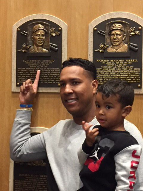 Royals catcher Salvador Perez holds his son Johan while pointing toward the Hall of Fame plaque of fellow Venezuelan Luis Aparicio. Perez visited the Hall of Fame on Nov. 10. (Bill Francis/National Baseball Hall of Fame and Museum)