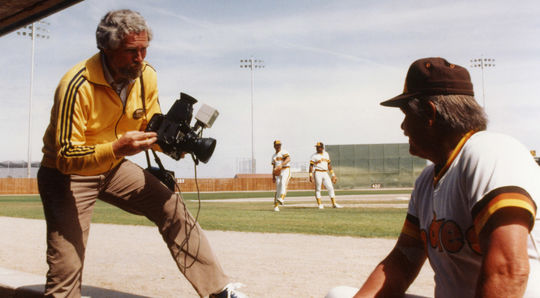 Topps photographer Doug McWilliams takes a picture of San Diego Padres manager and future Hall of Famer Dick Williams during Spring Training in Yuma, Ariz., in 1983. Over more than two decades, McWilliams took photographs of thousands of players and managers, many of which became images on Topps card that are now a part of the Hall of Fame's <em>Shoebox Treasures</em> exhibit. (Fred Kaplan/National Baseball Hall of Fame and Museum)