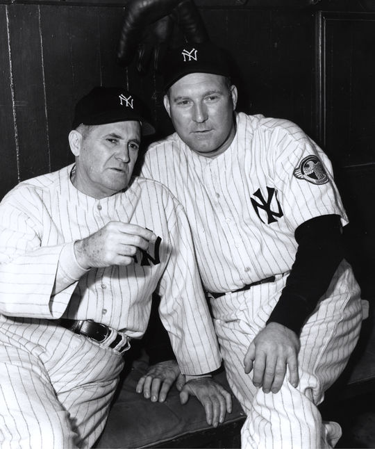 Red Ruffing (right) sits alongside fellow future Hall of Famer Joe McCarthy while sporting his ruptured duck patch on his sleeve. (Look Magazine/National Baseball Hall of Fame and Museum)