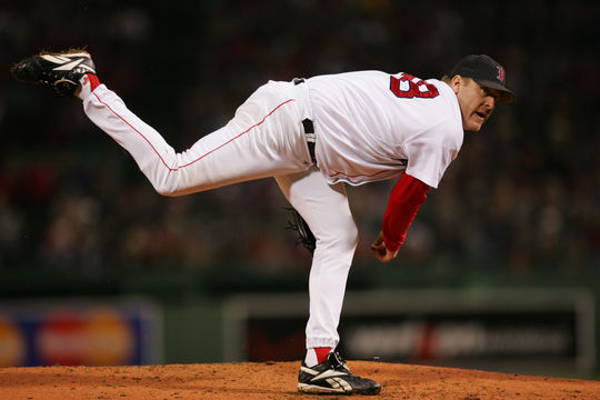 """Curt Schilling delivers a pitch in Game Two of the 2004 World Series with both the bloody sock and """"K ALS"""" mark visible near his right ankle. HY6N2184 (Brad Mangin / MLB)"""