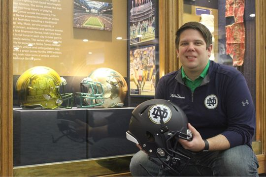 Mike Scholl, the associate athletics communications director at the University of Notre Dame, holds Cole Kmet's helmet that was donated to the Hall of Fame following a 2018 game at Yankee Stadium. Scholl was a 2008 Steele Intern at the Hall of Fame. (Sarah Higgins/Fighting Irish Media)