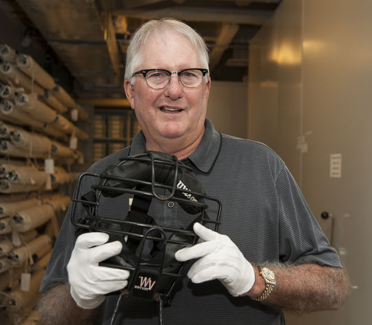 Steve Rippley poses with an umpire's mask used by Doug Harvey. (Milo Stewart Jr. / National Baseball Hall of Fame)