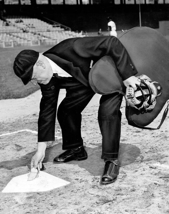 American League umpire Bill Grieve wipes off home plate. (National Baseball Hall of Fame)