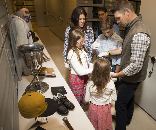 Kerry Wood and his family examine a Randy Johnson glove during their tour of the Hall of Fame on June 15, 2018. (Milo Stewart Jr./National Baseball Hall of Fame and Museum)