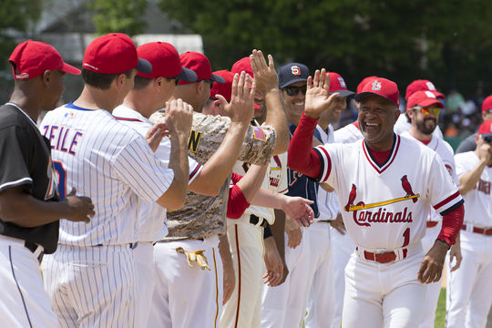 Hall of Famer Ozzie Smith high-fives his team at the start of the 2018 Hall of Fame Classic. (Milo Stewart Jr./National Baseball Hall of Fame and Museum)