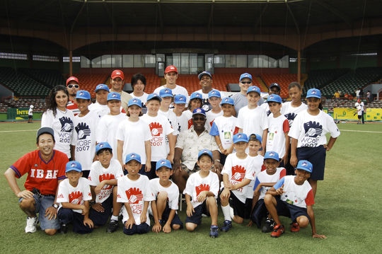 Hall of Famer Hank Aaron (center) takes a photo with participants at a 2007 event for the World Children's Baseball Fair (WCBF) in Puerto Rico. Aaron traveled to Puerto Rico with Japanese home run king Sadaharu Oh to help teach the game of baseball to children from around the world. (Milo Stewart, Jr. / National Baseball Hall of Fame)