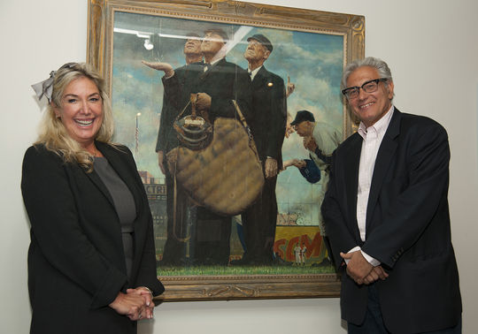 Cindy Lou Wakefield and Rick Friedman pose in front of Norman Rockwell's <em> Saturday Evening Post</em> illustration,<em> Tough Call</em>, in the Museum's Art Gallery. (Milo Stewart Jr. / National Baseball Hall of Fame)