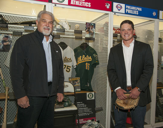 Phil Pohl poses with his father next to his artifacts on display at the Hall of Fame. (Milo Stewart Jr. / National Baseball Hall of Fame)