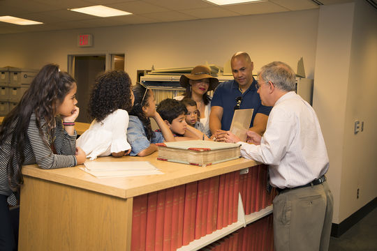 Carlos Beltrán and his family examine scrapbooks in the Museum during their tour of the Hall of Fame. (Milo Stewart Jr./National Baseball Hall of Fame and Museum)