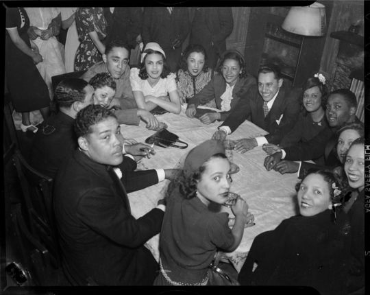 "Group, including boxer Joe Louis, Louis Jones, Jackie Ormes, Wendell Smith, Rosyln Lindsay, Louise Barnett, Gladys McCallogh, Cab Calloway, Betty Randolph Dorsey, Freddy Guinyard, Helen Matthews Ball, Elvira Guster, Wilmet, and Thelma Spangler gathered around table in Loendi Club, April 1938. Photo by Charles ""Teenie"" Harris. Courtesy of Carnegie Museum of Art."