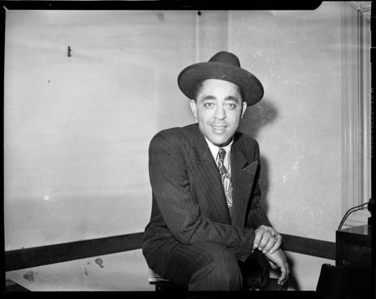 """Portrait of Pittsburgh Courier newspaper sports writer Wendell Smith wearing fedora, striped suit, and ring, posed in interior with chair rail, c. 1938-1945. Photo by Charles """"Teenie"""" Harris. Courtesy of Carnegie Museum of Art."""