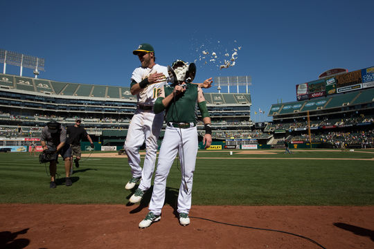 Jed Lowrie of the Oakland Athletics gets two pies in the face from teammate Josh Reddick while doing a television interview on the field after Lowrie drove in the winning run with a single in the bottom of the 9th inning against the Houston Astros at O.co Coliseum on Saturday, September 6, 2014 in Oakland, California. - BL-477789469BM (Brad Mangin / National Baseball Hall of Fame Library)