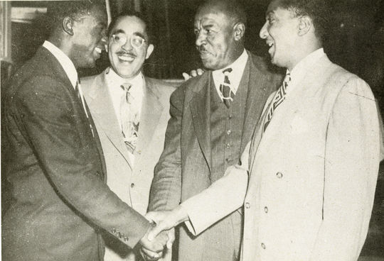 Photo from Jackie Robinson's first autobiography, <cite>My Own Story</cite>. Caption reads: 'Here are some of my closest pals in the Negro sports world. On my left are Wendell Smith, sportswriter for the <cite>Chicago Herald-American</cite> and the <cite>Pittsburgh Courier</cite>; Duke Slater, Iowa's All-American tackle; Ralph Metcalfe, famous Marquette sprinter.'