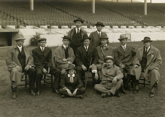 Baseball Writers at Polo Grounds 1911. (standing, left to right) John Wheeler (Herald) and John B. Foster (Evening Telegram); (seated in chairs) Sam Crane (Journal), Fred Lieb (Press), Damon Runyon (American), Bozeman Bulger (Evening World), Sid Mercer (Globe), Grantland Rice (Evening Mail) and Walter Trumbull (World). Seated on the ground is concessionaire Harry M. Stevens (right) and son Hal. - BL-915-2000 (Pach Brothers studio/National Baseball Hall of Fame Library)