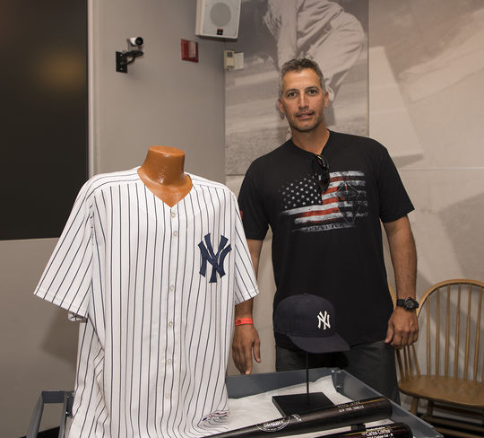 Andy Pettitte stands alongside his 2009 Yankees jersey -- a season in which he became the all-time winningest postseason pitcher in baseball history. To the right of the jersey is a cap that Pettitte wore when he and Mariano Rivera broke Dennis Eckersley and Bob Welch's record for win/saves with their 58th. (Milo Stewart Jr. / National Baseball Hall of Fame and Museum)